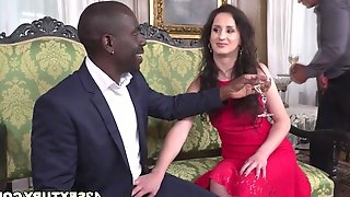 Mature slut is enjoying getting banged by a black stud with monster cock and his white strapping friend on the couch